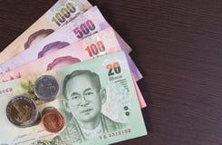 Cédula tailandesa do dinheiro e moeda tailandesa na madeira da testa Imagem de Stock Royalty Free