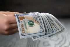 Cédulas adolescentes fêmeas do dólar da posse da mão Foto de Stock Royalty Free