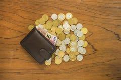 Cédulas brasileiras na carteira e moedas no fundo de madeira Fotografia de Stock Royalty Free