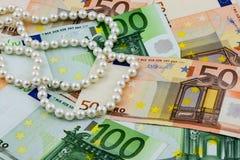 Cédulas da riqueza, do Euro e pérolas reais Fotos de Stock