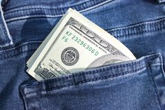 Cédulas das centenas de dólares americanos que colam fora de um bolso das calças de brim Imagens de Stock