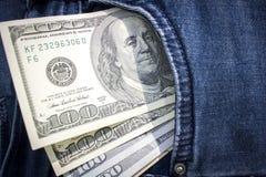 Cédulas das centenas de dólares americanos que colam fora de um bolso das calças de brim Imagem de Stock Royalty Free