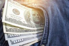 Cédulas das centenas de dólares americanos que colam fora de um bolso das calças de brim Moeda americana Fotos de Stock Royalty Free