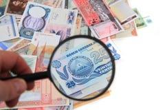 cédulas diferentes do dinheiro com para ampliar o vidro imagens de stock
