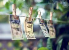 Cédulas do dólar americano que penduram no conept da lavagem de dinheiro da corda Fotografia de Stock