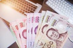 Cédulas do dinheiro e trabalho e dinheiro tailandeses do laptop fotografia de stock
