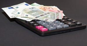 Cédulas do dinheiro europeu e de máquina calculadora no fundo preto Fotos de Stock
