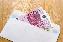 Cédulas do Euro em um envelope branco em um fundo de madeira bribe fotos de stock royalty free