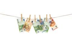 Cédulas do Euro que penduram na corda no fundo branco Imagens de Stock Royalty Free