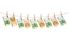 Cédulas do Euro que penduram na corda no fundo branco Foto de Stock