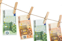 Cédulas do Euro que penduram na corda no fundo branco Imagem de Stock Royalty Free