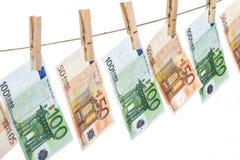 Cédulas do Euro que penduram na corda no fundo branco Foto de Stock Royalty Free