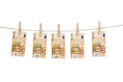50 cédulas do Euro que penduram na corda no fundo branco Foto de Stock