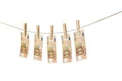 50 cédulas do Euro que penduram na corda no fundo branco Fotografia de Stock Royalty Free