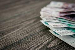Cédulas do rublo de russo, dinheiro no fundo de madeira escuro Imagens de Stock