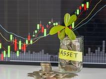 100 cédulas dos dólares americanos e moedas do dinheiro com dinheiro no frasco contra o fundo do sumário do mercado de valores de Fotografia de Stock Royalty Free