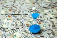 Cédulas dos dólares da ampulheta e do dinheiro Tempo é dinheiro imagens de stock