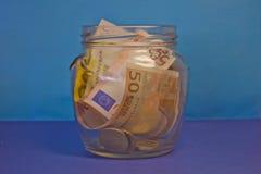 Cédulas e moedas em um frasco de vidro Fotografia de Stock