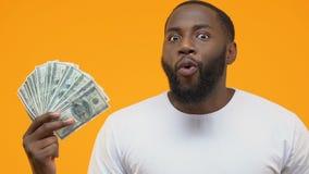 Cédulas entusiasmados do dólar da exibição do indivíduo preto, serviço fácil do crédito, salário do salário vídeos de arquivo