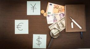 Cédulas internacionais, moedas, bloco de notas, etiquetas com sinais de moeda na tabela de madeira Fotos de Stock Royalty Free