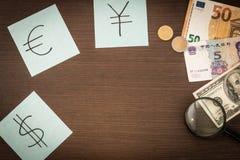 Cédulas internacionais, moedas, bloco de notas, etiquetas com sinais de moeda na tabela de madeira Copie o espaço Foto de Stock Royalty Free