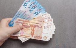 Cédulas novas do russo denominadas em 2000 e 5000 rublos no close-up das mãos do homem Imagem de Stock