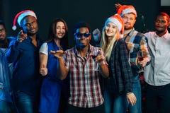 Célébrant la nouvelle année ensemble Groupe des beaux jeunes dans des chapeaux de Santa Photographie stock