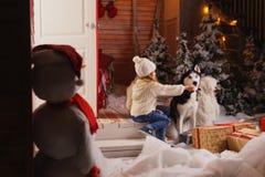 Célébrant Noël avec leur chien à la maison jeu d'enfants avec le chien avec l'arbre de Noël décoré à l'arrière-plan Photographie stock