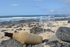 Célébration avec deux verres et bouteilles de vin sur la plage Photographie stock