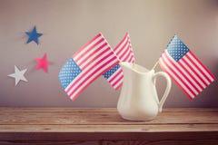 Célébration de Jour de la Déclaration d'Indépendance des Etats-Unis Drapeaux des Etats-Unis dans la cruche sur la table en bois Photographie stock