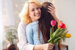 Célébration de mère et de fille ensemble à la maison se tenant étreignante jugeant le sourire de fleurs heureux photographie stock libre de droits