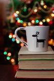 Célébration de Noël avec la tasse et le boîte-cadeau sur des livres au-dessus de bokeh Image libre de droits