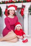 Célébration de Noël ou de nouvelle année Mère et fille heureuses dans le chapeau rouge de Santa se reposant près de l'arbre de No Photographie stock
