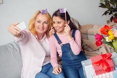 Célébration de petite-fille et de grand-mère à la maison se reposant prenant des photos de selfie sur le smartphone joyeux Photos stock