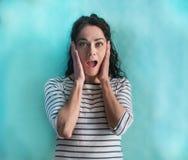 Célébration de port de chandail de rayures de belle femme hispanique folle et stupéfaite pour le succès avec des bras augmentés e image libre de droits