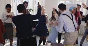 Célébration de victoire sur le lieu de travail moderne sain Jeune danse femelle heureuse enthousiaste de patron avec les collègue banque de vidéos
