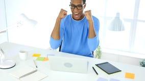 Célébration du succès tout en travaillant sur l'ordinateur portable, excitation photo stock