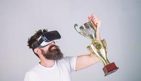 Célébrez la victoire Le casque barbu de vr de hippie d'homme tient le gobelet d'or Victoire de sensation dans des jeux de réalité photos libres de droits