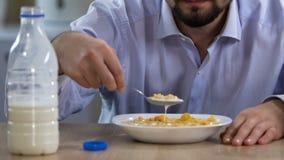 Célibataire mangeant des flocons avec du lait pendant le matin avec dégoût, la maladie d'estomac banque de vidéos