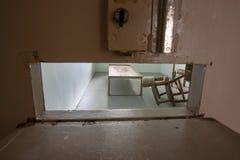 Célula de la reclusión solitaria a través del listón de la puerta fotos de archivo