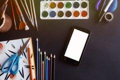 Célula de Smartphone con la pantalla blanca vacía y el pai colorido de los lápices foto de archivo libre de regalías