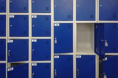 Células en un almacenamiento azul del equipaje del color con llaves y un fondo de la puerta abierta imagen de archivo
