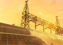 Células solares en la central eléctrica con la subestación eléctrica de alto voltaje de los pilares del pilón en puesta del sol Foto de archivo