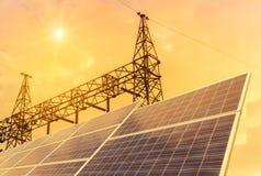 Células solares en la central eléctrica con la subestación eléctrica de alto voltaje de los pilares del pilón en puesta del sol Fotos de archivo