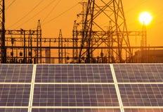 Células solares en la central eléctrica con la subestación eléctrica de alto voltaje de los pilares del pilón en puesta del sol Fotografía de archivo libre de regalías