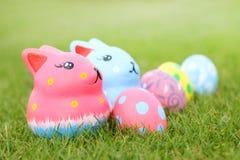 céntrese el conejo colorido con los huevos en hierba el día de Pascua Foto de archivo