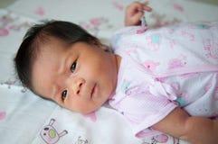 Céntrese en el bebé asiático mientras que duerme y juega en la cama/cercano para arriba en recién nacido lindo está mirando la cá Imagen de archivo libre de regalías