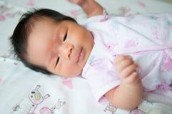 Céntrese en el bebé asiático mientras que duerme y juega en la cama/cercano para arriba en recién nacido lindo está mirando la cá Foto de archivo libre de regalías