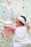 Céntrese en el bebé con la venda agradable mientras que dormita y juega con la muñeca linda en la cama La muchacha recién nacida  Fotos de archivo libres de regalías