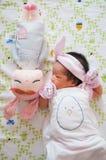 Céntrese en el bebé con la venda agradable mientras que dormita y juega con la muñeca linda en la cama La muchacha recién nacida  Imagen de archivo libre de regalías